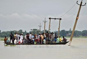 Villagers cross a flooded road at Asigarh village in Morigaon district in Assam