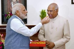 Prime Minister Narendra Modi offers sweet to Ram Nath Kovind on being elected as the 14th President of India, in New Delhi on Thursday.