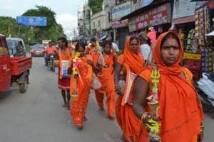 The women clad in saffron and holding their kanwars head to Dashashwamedh ghat
