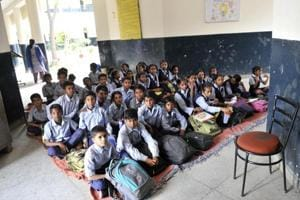 Students attend class in a corridor of their school. Many schools across India have become run-down versions of themselves. (HTFile Photo)