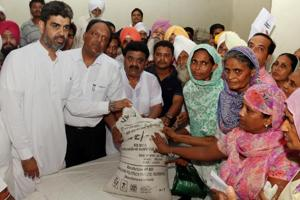 Jaijeet Singh Johal, brother-in-law of Punjab finance minister Manpreet Singh Badal,handing over wheat bags to atta-dal scheme beneficiaries in Bathinda on Monday.