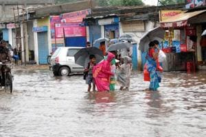 School children returning home through waterlogged Ratu road after heavy rain in Ranchi