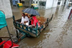 People sit in a tractor trolley as they move out of a flooded neighbourhood after heavy rain in Ahmedabad, India, July 24, 2017.