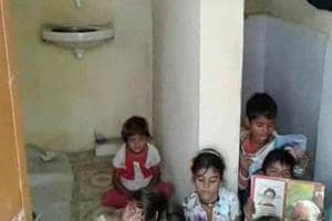 Students in a primary school in a village in Neemuch district in Madhya Pradesh studying inside a disused toilet because there is school building.