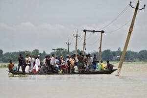 Villagers use a boat to cross a flooded road at Asigarh village in Morigaon district in the northeastern state of Assam.