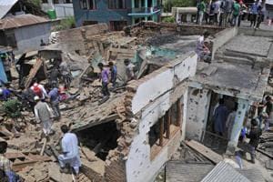 Villagers gather near the destroyed house where the militants were trapped in Hakripora in Kashmir's Pulwama district on Tuesday, August 1. (Waseem Andrabi / HTPhoto)
