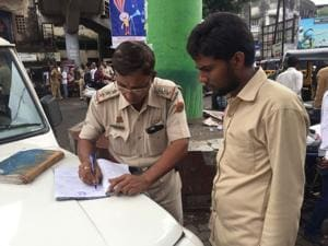 A traffic police officer books an auto driver outside Dombivli stationon Wednesday.