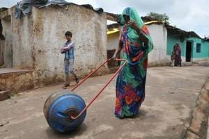 """A woman uses a """"water wheel""""- a drum that doubles up as a wheel, attached to two handles- to take water home in Madhya Pradesh's Vidisha district."""