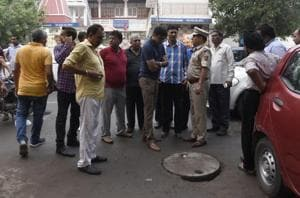 Police speak to people gathered at a manhole where three sanitation workers lost their lives while cleaning a sewer at Jal Vihar, Lajpat Nagar, in New Delhi, on  August 06, 2017.