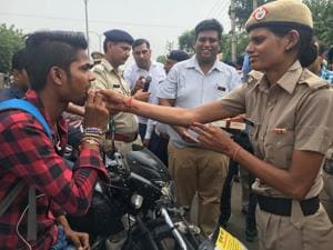 Women police officers tie rakhis to traffic violators in Gurgaon, in return of a safety pledge to follow the road rules.
