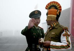 (FILES) This file photo taken on July 10, 2008 shows a Chinese soldier (L) gesturing next to an Indian soldier at the Nathu La border crossing between India and China in Sikkim. China has stepped up its rhetoric in an increasingly tense border row with India.