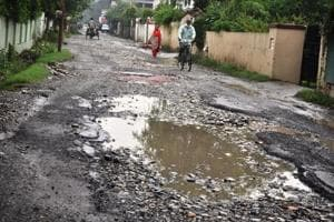 A view of pothole filled Canal Road in Dehradun.