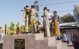 People garland a statue of constable Khumaram, who was killed by Anandpal gang, in Nagaur.