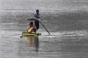 Villagers travel on a raft through flood waters in Hatilung village in Lakhimpur district, about 380 km from Guwahati, in Assam on Saturday.