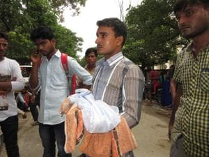 A man holds a dead baby outside the BRD Medical College in Gorakhpur, Uttar Pradesh. The jury is out on whether the 63 such deaths here this past week were a result of callousness, negligence or disease, but there's no getting away from the fact that the children would still be alive if they had not contracted encephalitis.