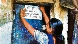 A Pardhi woman pasting a poster asking police not to pick up people from their homes while they are sleeping.ht photo