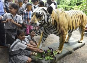 School children tie rakhi to dummy Royal Bengal Tiger during the International Tiger Day at Delhi Zoo.