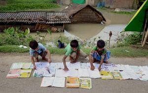School students laid their books on the road for drying in a flood-affected village in Morigaon district of Assam.
