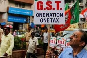 A BJP supporter  holds a placard during a rally in favour of the goods and services tax.