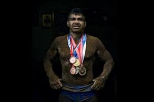 Deaf Olympic Gold medalist wrestler Virender Singh poses for a portrait with his medals at his akhara near Sadar Bazar in New Delhi.