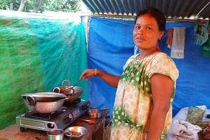 A flood affected resident of Morigaon district tries to cook a meal for her family at a makeshift camp on Wednesday.