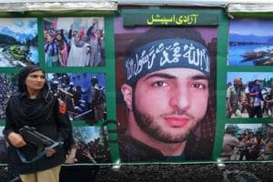 Policewomen stand guard beside a poster with the image of slain Hizbul Mujahideen commander Burhan Wani which adorns a carriage of the Azadi Train at the time of its inaugural journey in August 2016.