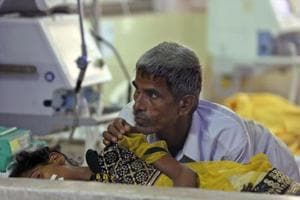 A man attends to a child receiving treatment at the state-run Baba Raghav Das Medical College Hospital in Gorakhpur, Uttar Pradesh, on August 13, 2017.