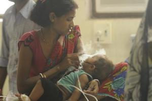 A woman tends to her child inside the encephalitis ward at BRD Medical College in Gorakhpur. (Deepak Gupta/ HT photo)
