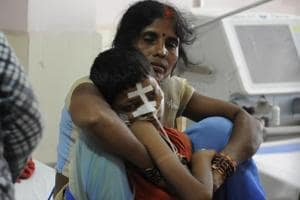 A mother cradles her child inside the encephalitis ward at BRD medical centre in Gorakhpur, on August 15, 2017.