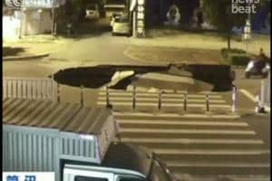 Watch: Sinkhole appears in middle of the road, sinks biker glued to...