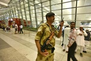 A securityman at the Delhi airport talks on walkie-talkie even as passengers look on. The airport saw a brief pause in operations on Sunday after a pilot raised an alarm about a drone-like object.