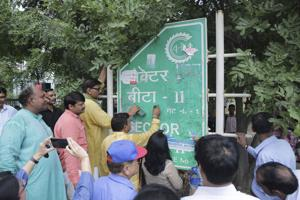 MLA Jewar removes posters from a signage in Greater Noida.
