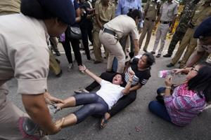 Police detain Gorkha people who were staging a protest for separate state of Gorkhaland, at Rajpath near Parliament house in New Delhi on Friday.
