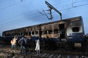 People stand next to a burned out train coach that had been set alight by supporters of a controversial guru, who had earlier been convicted of rape, at Anand Vihar railway station in New Delhi on August 25, 2017.