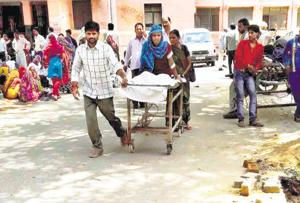 A patient being carried by relatives on a stretcher at SN Hospital in Agra