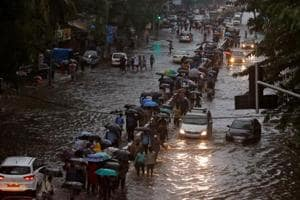Commuters walk through water-logged roads after rains in Mumbai on August 29, 2017.