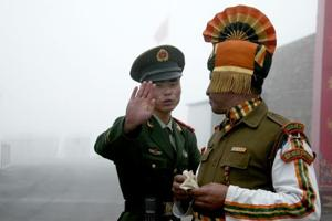 (FILES) This file photo taken on July 10, 2008 shows a Chinese soldier (L) gesturing next to an Indian soldier at the Nathu La border crossing between India and China in India