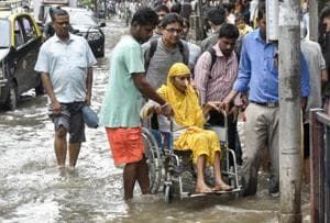 People help a patient pass a waterlogged street at Lower Parel.