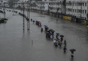People walk on a submerged railway track at Matunga on Tuesday.