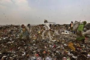 File photo of an MCD worker chasing away ragpickers at the Ghazipur landfill site in east Delhi.