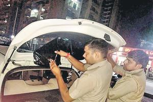Cops removing black film from cars in Noida.
