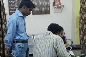 The accused, Durgesh Aggarwal (left) at a  police station after his arrest for making obscene calls to 300 policewomen.