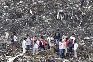 People gathered at the garbage mound in east Delhi's Ghazipur. A part of this 'trash mountain' collapsed into a canal on September 1 killing two persons.