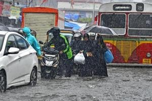 People struggle on waterlogged roads in Mumbai on August 29.