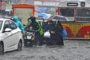 People struggle on waterlogged roads in Mumbai on August 29.