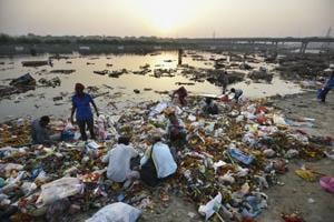 Locals scavenge for the remains of idols in the Yamuna after Durga Puja in New Delhi on October 12, 2016.