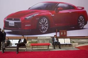Exhibitors sit and talk under the Nissan GTR luxury car billboard during an Auto Expo in Greater Noida on February 3, 2016