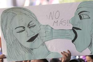 A woman holds a sign that reads No More during a rally against abuse and domestic violence