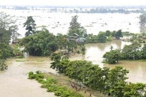 Flood-affected people gather below a helicopter carrying relief materials in flooded areas of Sonitpur district of Assam. (Reuters file photo / Representational)