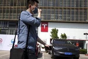 In this file photo, a man wears a mask walks past a Tesla electric vehicle showroom and charging station in Beijing, China.